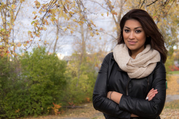 Attractive Hispanic woman posing with arms cross outside during