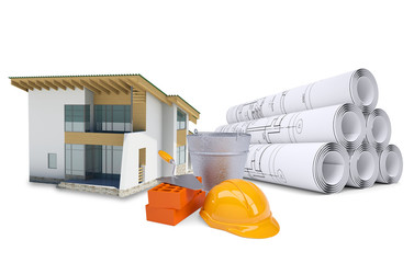 Small model house near scrolls of architectural drawings and