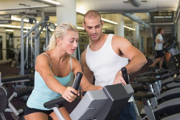 Trainer assisting woman with exercise bike at gym