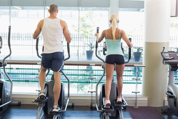 Rear view of couple working on x-trainers at gym
