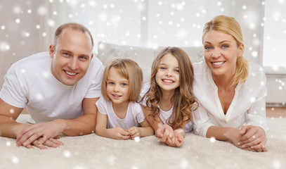 smiling parents and two little girls at home