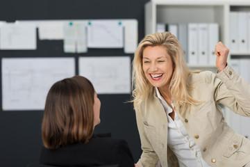 zwei lachende kolleginnen im büro