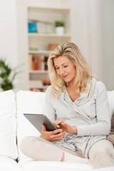entspannte frau tippt zuhause auf dem tablet-pc