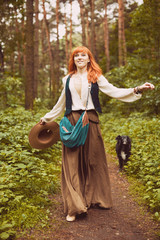 Romantic hippie woman with dog smile in the woods.