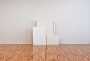 Three blank canvases and frames on a wooden floor