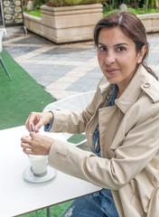 Brunette woman drinking a cofee