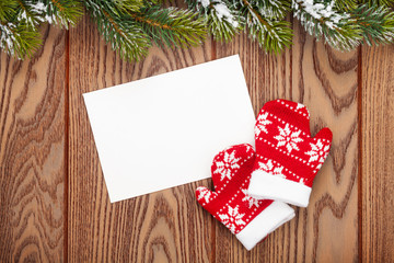 Christmas greeting card or photo frame and mittens over wooden t