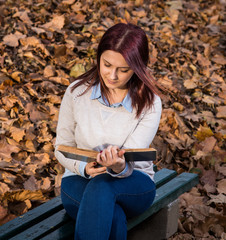 University girl sitting in park and reading a book