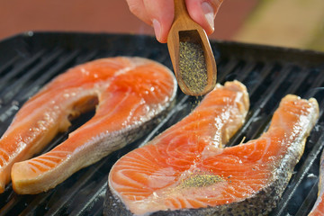 Portion of fresh salmon fillet with herbs on a grill