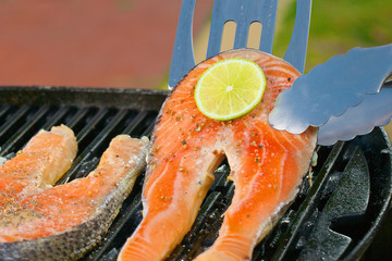 Portion of fresh salmon fillet with lime on a grill