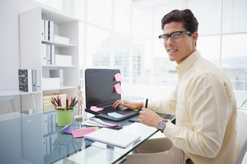 Designer using laptop and smiling at camera