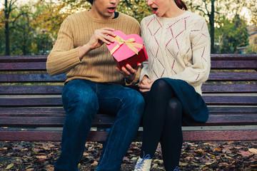 Couple opening heart shaped box