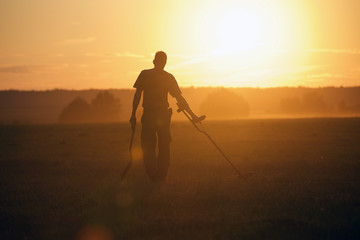 Treasure hunter with Metal detector in the field on the sunset