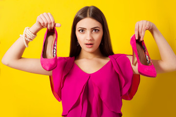 Beautiful girl with long hair with purple shoes in her hand