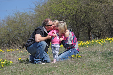 Happy mother, father kissing theirs daughter in the nature