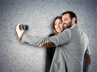 Man photographing with his girlfriend over textured background