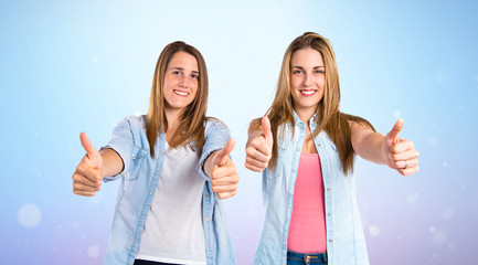 Friends with thumbs up over blue background