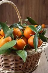 mandarini con foglie in cesto su tavolo di legno