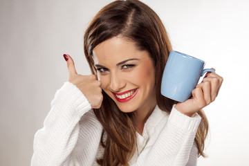 beautiful young woman holding a cup of tea and showing thumbs up