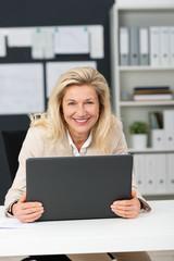 lachende ältere geschäftsfrau mit laptop