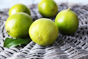 Fresh juicy limes on wicker background