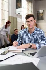 junger mann sitzt am schreibtisch mit laptop und unterlagen