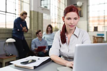 junge frau arbeitet am computer mit team im hintergrund