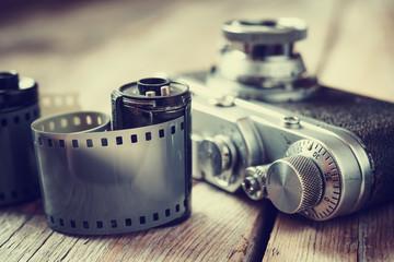 Old photo film rolls, cassette and retro camera, selective focus