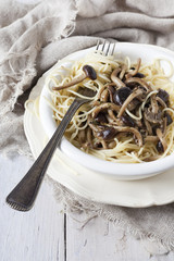 forkful of pasta spaghetti with pioppini mushrooms on plate