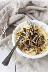 forkful of pasta spaghetti with fresh pioppini mushrooms