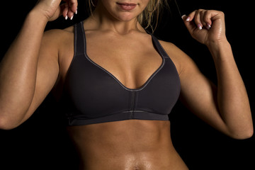 woman chest in black sports bra arms up