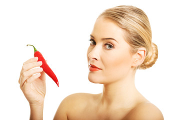 Portrait of nude woman holding chilli
