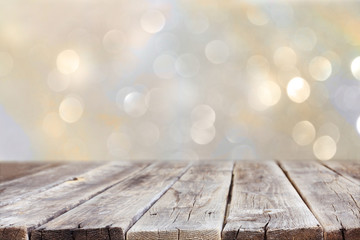 rustic wood table in front of glitter silver and gold bright bok