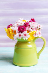 Beautiful flowers in pitcher on table on purple background