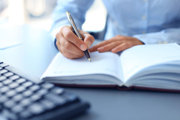 businessman writes in a notebook while sitting at a desk