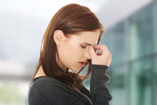 Woman suffering for sinus pain or migraine headache.