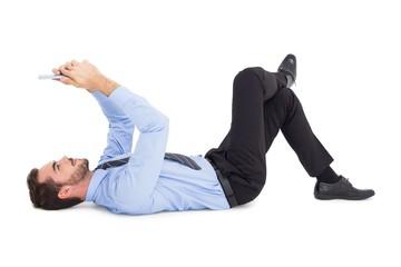 Cheerful businessman lying on floor using tablet