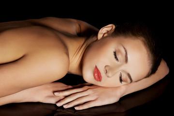 Portrait of lying nude woman on dark background
