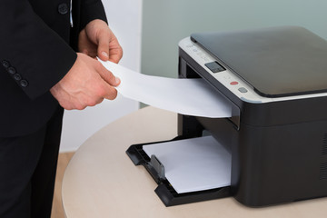 Businessman Holding Paper While Using Photocopy Machine