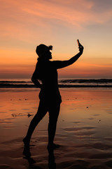 Silhouette of Thai Woman using smartphone at the beach in sunset