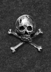 Metal skull and bones on gray background