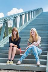Two girls sitting on metal bridge