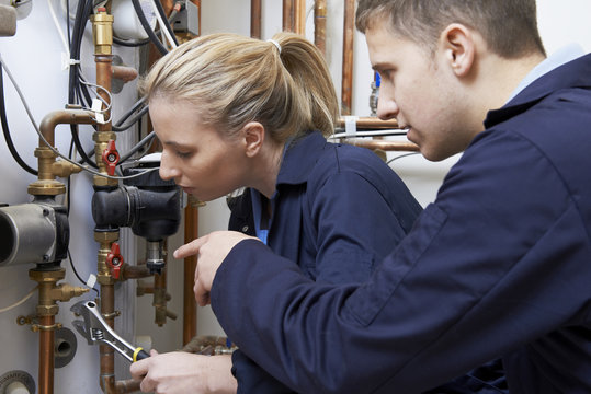 Female Trainee Plumber Working On Central Heating Boiler