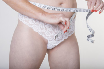Woman measuring her waistline with a tape measure