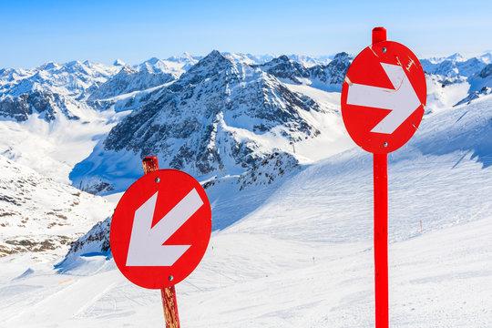 Red signs on ski slope in ski resort of Pitztal, Austrian Alps