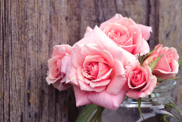 Pink roses against a woodwall with a retro filter effect