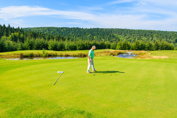 Mature man plays golf in Arlamow hotel, Bieszczady Mountains