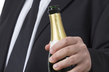 Man in suit with open Champagne bottle