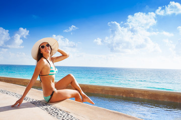 Happy woman in sunglasses with white hat sunbathes