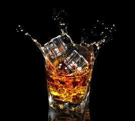 Glass of whiskey with splash on black background